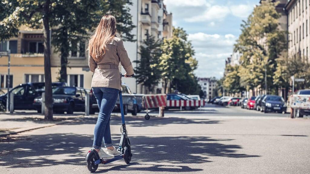 kvinde kører på elektrisk løbehjul på gaden