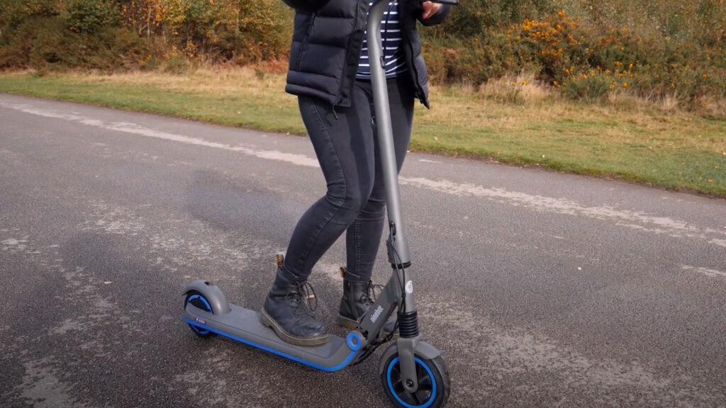 kvinde står med segway ninebot zing e10 el-løbehjul til børn og teenagere