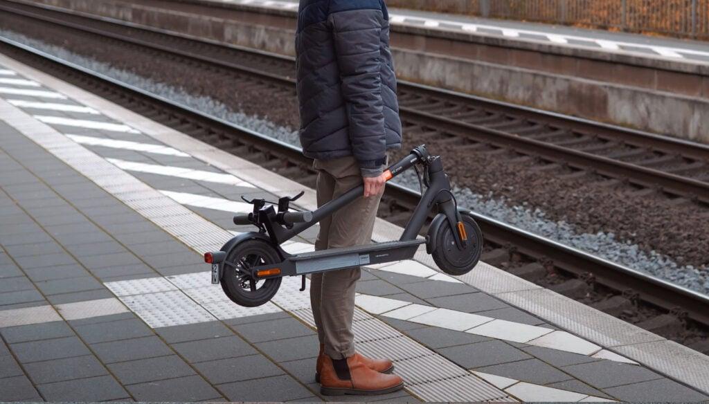 mand står med sammenfoldet xiaomi 1s løbehul og venter på toget