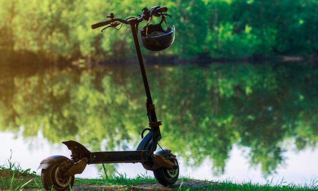 off-road el-løbehjul står ved en sø med en hjelm på styret
